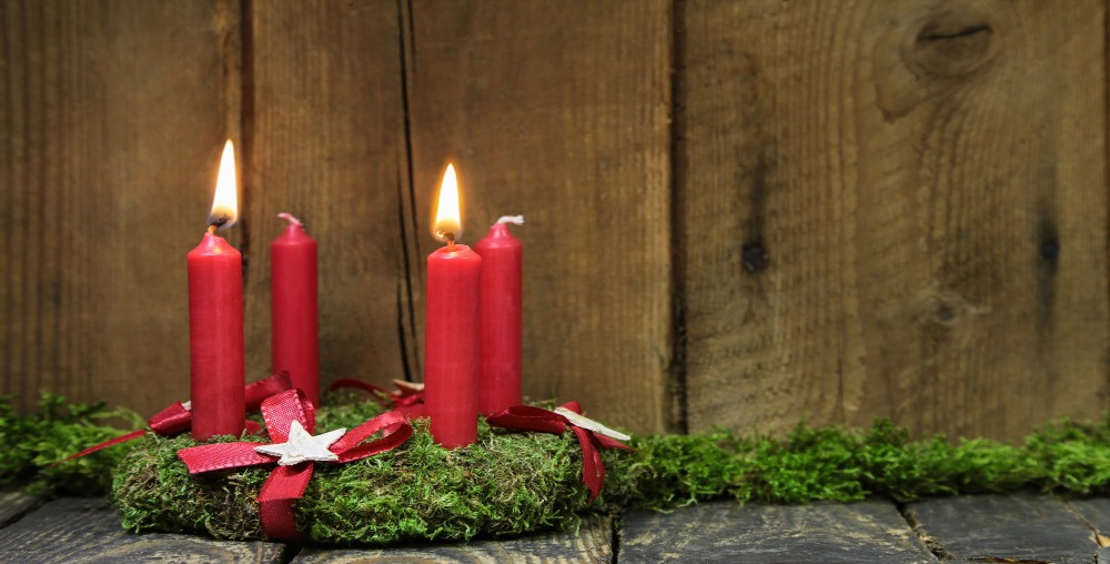 Advent or christmas wreath with four red wax candles on wooden background.